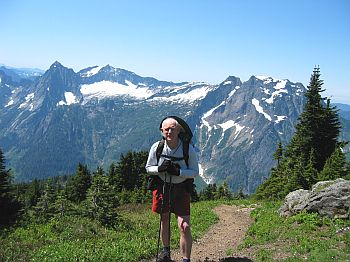 Charles, at the summit of Mt. Dickerman, with Big Four Mountain, and Vesper & Sperry Peaks in the background.